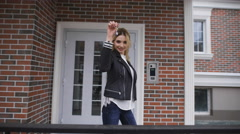 Beautiful blonde shows the keys to their new apartments in a stylish brick house Stock Footage