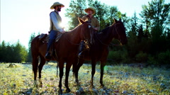 Cowboys at sunset Riding horses in valley wilderness area Canada Stock Footage