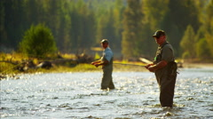 River wading males freshwater fly fishing in American Wilderness Stock Footage