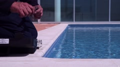 Worker taking water samples from pool for quality control Stock Footage
