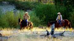 Riders on horse in valley stream Rocky mountains USA Stock Footage