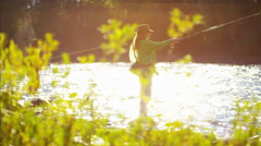 Skilled hobby female and male casting line freshwater fishing USA Stock Footage
