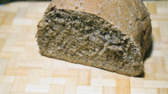 Rye-wheat bread is cut with a knife on a board Stock Footage