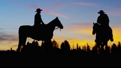 Silhouette reveal of Cowboy Riders in sunset wilderness USA Stock Footage
