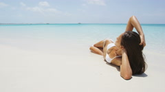 Suntan bikini woman relaxing on beach vacation Stock Footage