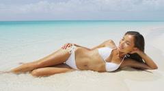 Beach bikini body - sexy slim woman on vacation sunbathing tanning in water - stock footage