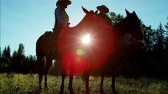 Sunrise silhouette of cowboys riding horses in valley wilderness area Canada Stock Footage