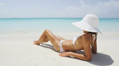 Beach vacation woman in summer hat and bikini sitting in sand sunbathing Stock Footage