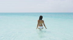 Bathing and swimming beach vacation woman walking in turquoise ocean Stock Footage