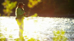 Female using rod and reel casting line in freshwater river Canada - stock footage