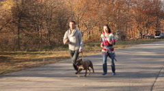 Happy Couple With Dog Running In Autumn Park Stock Footage
