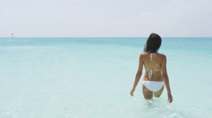 Swimming bathing beach vacation woman walking in turquoise ocean water Stock Footage