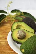 Fresh green cutted avocados with leaves Stock Photos