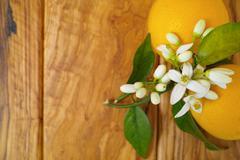 Fresh oranges with leaves and orange tree flowers on olive wood - stock photo