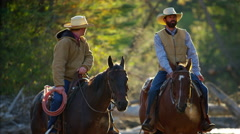 Cowboys Riding horses in the river wilderness area Canada Stock Footage