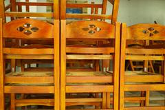Heap of chairs in closed cafe, out of season in Greece Stock Photos