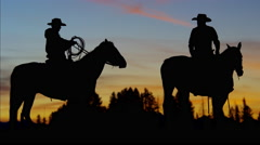 Silhouette sunrise of Cowboy Riders in sunset wilderness Stock Footage
