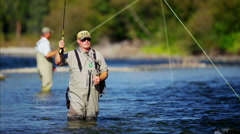 Fisherman using rod and reel casting line in freshwater river Canada - stock footage