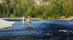 Fisherman fly fishing in Canadian river casting using rod and reel Stock Footage