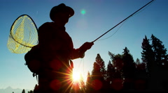 Sunrise silhouette of man fishing for Cutthroat Trout in freshwater river - stock footage