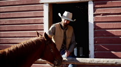 Cowboy Ranch hand with horse on Dude Ranch in Corral USA Stock Footage