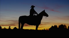 Silhouette of Cowboy Rider at sunset Wild West area Canada Stock Footage