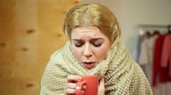 Diseased girl warming herself with hot tea, feeling sick. Healthcare, illness Stock Footage