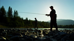 Fisherman in sunrise silhouette with rod and reel casting line freshwater river Stock Footage