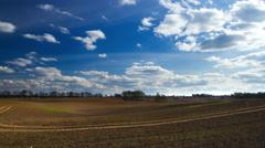 Plowed field landscape under blue sky with clouds, 4k timelapse Stock Footage