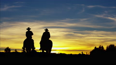 Silhouette of Cowboy Riders in sunset wilderness Canada Stock Footage