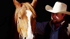 Stock Video Footage of Portrait of a cowboy ranch hand bonding with horse on Dude Ranch USA