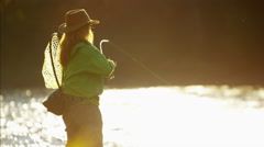 Female using rod and reel casting line in freshwater river Canada Stock Footage