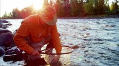 Fisherman with catch in keep net freshwater river Canada Stock Footage