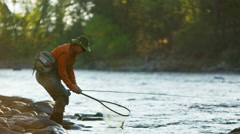 Rod and reel fisherman casting line in freshwater river USA Stock Footage