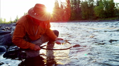 Portrait fisherman with fish in keep net freshwater river Canada Stock Footage