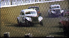 1957: Classic car stock racing infield behind flimsy safety fence. Stock Footage
