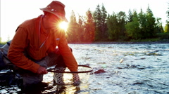 Portrait of fisherman with catch in keep net freshwater river Canada Stock Footage