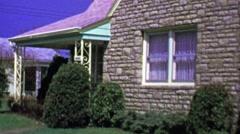 1964: Quaint brick facade bungalow suburban house garage driveway. Stock Footage