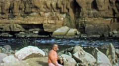 1964: Woman sitting on rock near wild western USA canyon river. Stock Footage