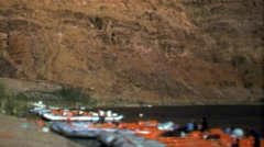 1964: River rafting trip boats ashore while people take lunch. Stock Footage