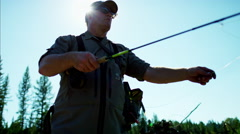 Rod and reel fisherman casting line in freshwater river USA - stock footage