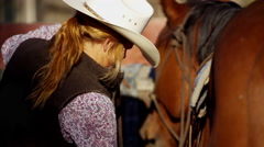 Cowboy in corral saddling his horse Dude Ranch Canada Stock Footage