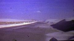 1957: Winter snow drift blows across barren road landscape. - stock footage