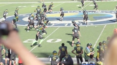 Watching youth boys football game from stadium bleachers - stock footage