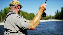 Fisherman using rod and reel casting line in freshwater river Stock Footage