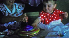 1957: Mom baby spinning top toy gift play learning centrifugal force. Stock Footage