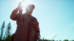 Fisherman in silhouette using rod and reel casting line in freshwater river Stock Footage