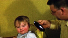 1957: Dad cuts bold baby hair with electric buzzers shaves head. Stock Footage