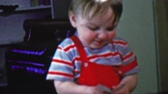 1957: Baby playing poker cards holds hand confused about betting. - stock footage