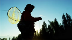 Sunrise silhouette of man with keep net freshwater fishing in river Canada Stock Footage